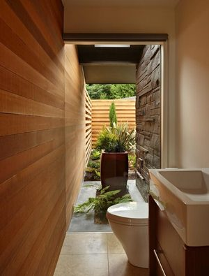 The bathroom has a Zen quality with a window wall into the courtyard. The cedar siding travels to that wall and just keeps on going into the room, further breaking the barrier between indoors and out.