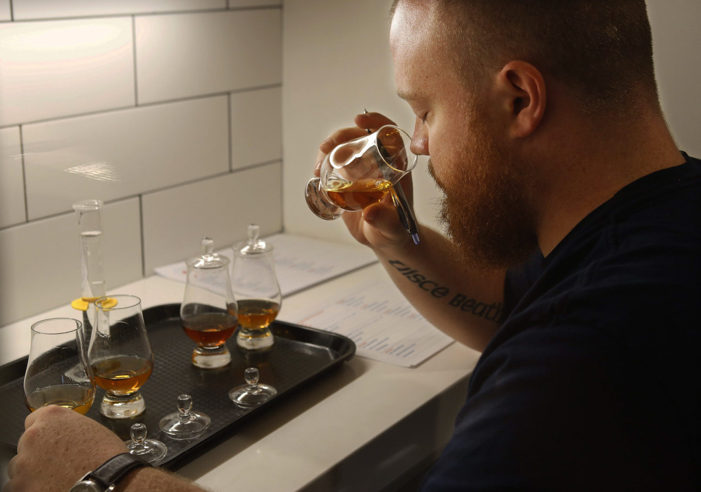 Matt Hofmann, master distiller and co-founder at Westland Distillery, samples from several batches of whiskey to determine their characteristics. (Mark Harrison / The Seattle Times)