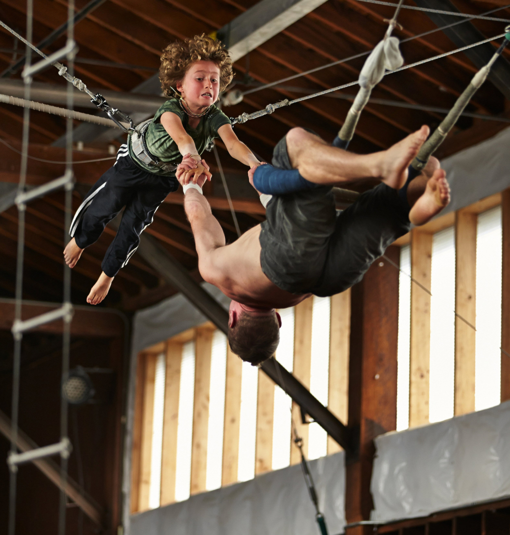 At the open level trapeze class, Jackson Burger, 8, does a mid-air transfer and is caught by instructor Jesse Lenihan, at Emerald City Trapeze Arts in South Seattle. (Benjamin Benschneider / The Seattle Times)