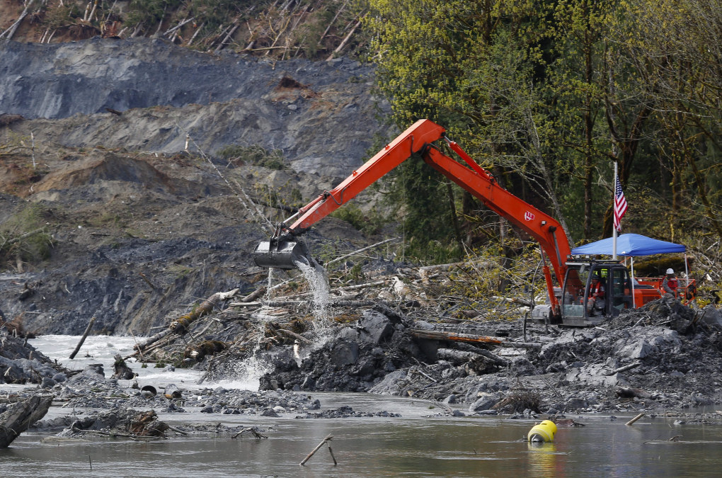 An amphibious excavator from BCI Contracting, hired by Snohomish County, brings up a bucketful of water and mud as it helps widen what is now the North Fork Stillaguamish River channel near the slide on Wednesday, April 23, 2014. (Lindsey Wasson / The Seattle Times)