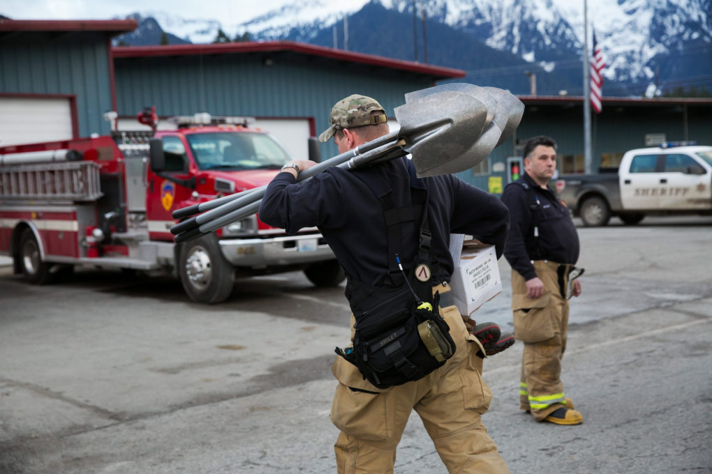 Firefighters help unload publicly donated equipment to aid the recovery operations at the Darrington Fire District 24 Station on Thursday, March 27, 2014. (Marcus Yam / The Seattle Times)