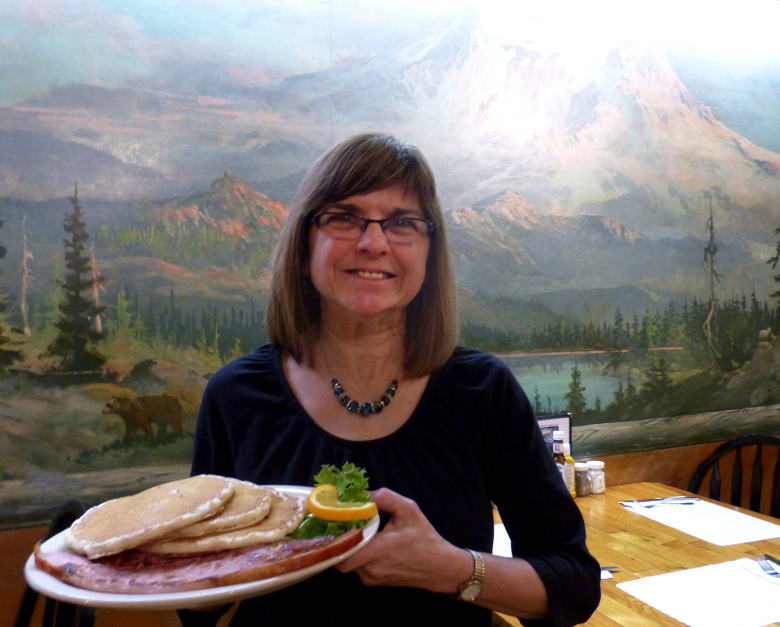 Server Kathy Anderson delivers a breakfast special — blueberry pancakes and a giant slab of ham — in the dining room at Copper Creek Inn. A hand-painted mural of Mount Rainier decorates a wall.  (Brian J. Cantwell/The Seattle Times)