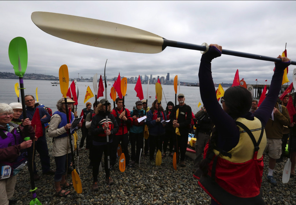 Paddle up signals halt, demonstrates Zarna Joshi with Rising Tide Seattle, who was giving instructions to kayakers on the beach at Seacrest Park in West Seattle.  (Alan Berner / The Seattle Times)