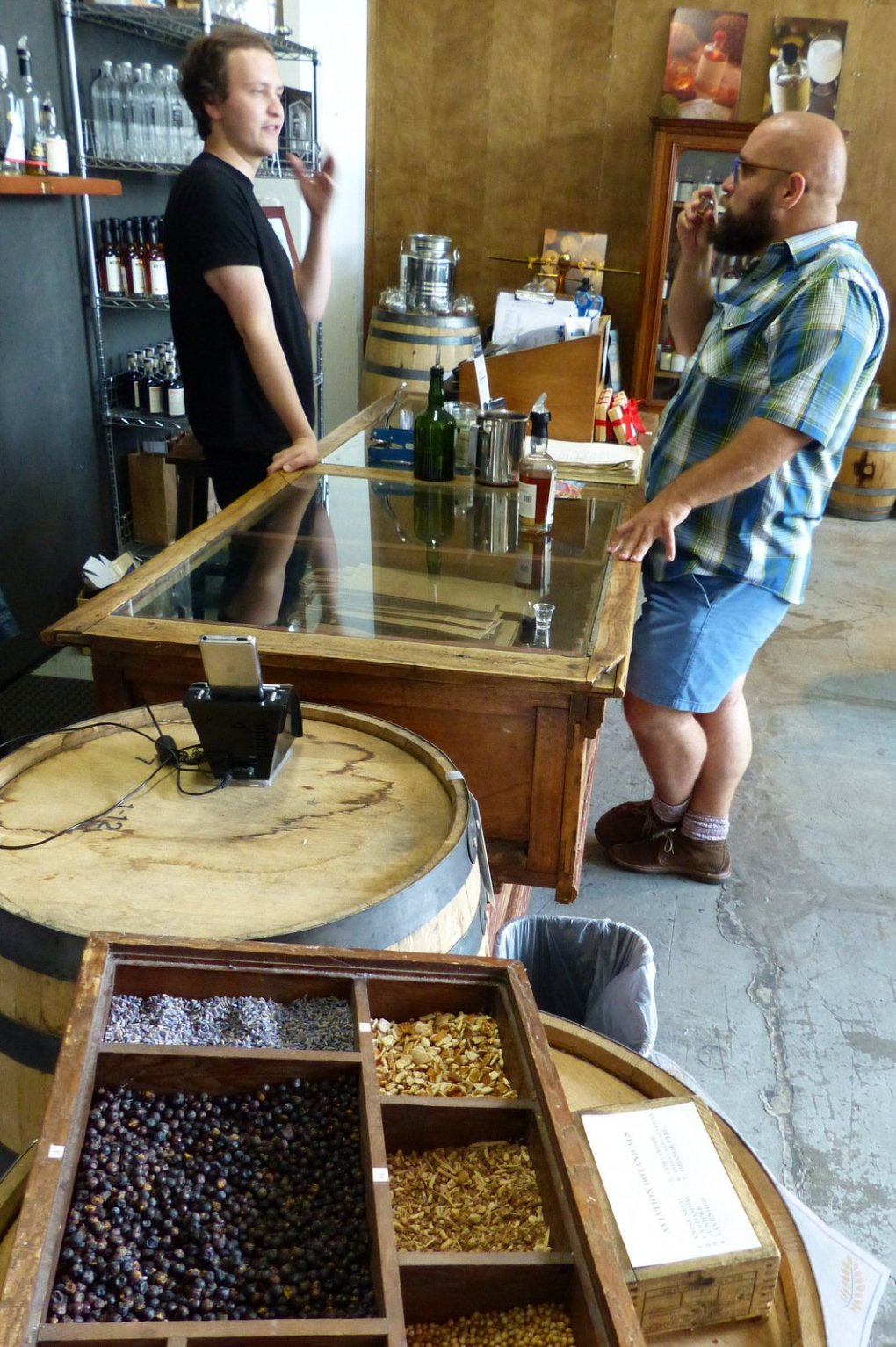Dimitriy Masterov, visiting from Los Gatos, Calif. (right), samples wares with the help of bartender Zak Nelson at House Spirits Distillery, part of Portland's Distillery Row. In the foreground are flavoring agents for the distillery's gin, including anise seed, cardamom, juniper berries, lavender, coriander, Indian sarsaparilla and orange peel.  (Brian J. Cantwell/The Seattle Times)