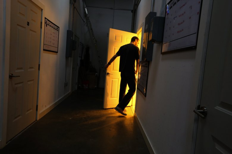 J.J. West, master grower at Coastal Cannabis in Seattle, enters a brilliantly lit grow room. (Ken Lambert/The Seattle Times)