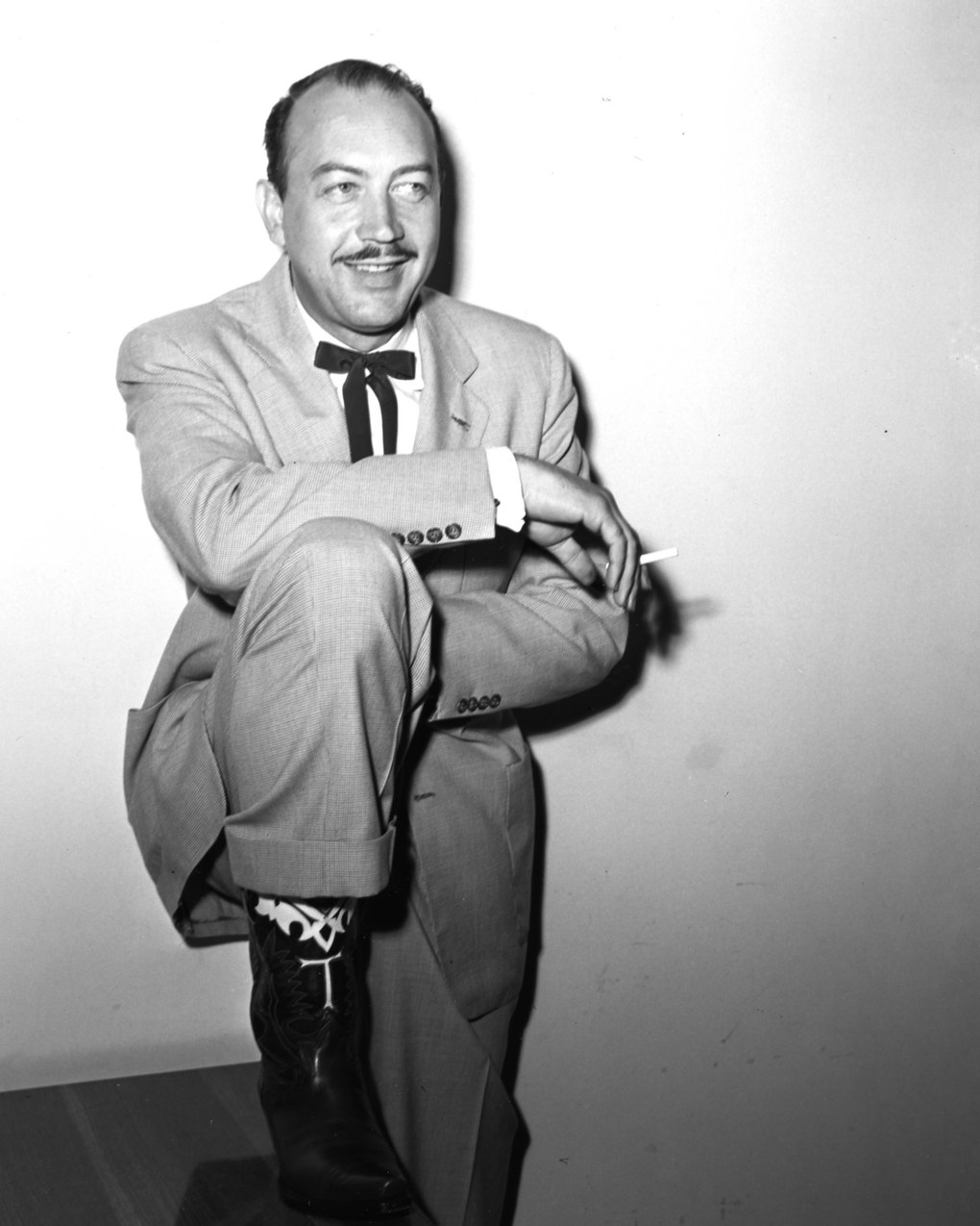 """In this image taken circa 1952, shows Tex in the custom-made cowboy boots he had made especially before each test flight.  Along with his cowboy style of dress, his maverick behavior is said to have inspired the creation of Dr. Strangelove's Maj. T.J. """"King"""" Kong character, who, in rodeo style, rode a balky nuclear weapon to its target.   ( The Boeing Company)"""