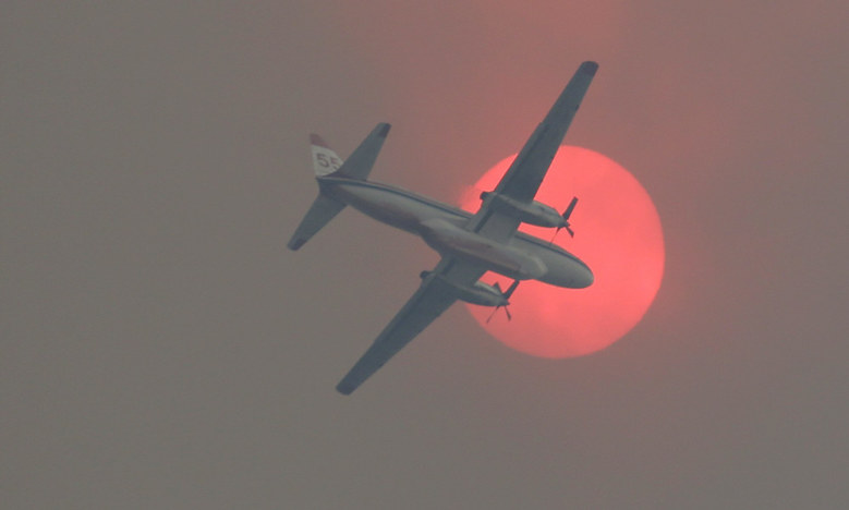 A fire-retardant plane passes in front of the sun, which appeared orange Wednesday from wildfire smoke. (Ted S. Warren / The Associated Press)