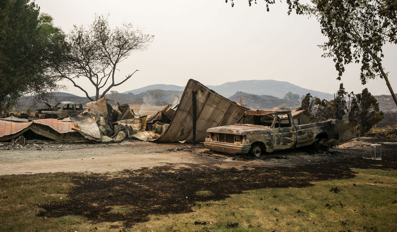 Burned-out trucks and a mobile home sit along Johnson Creek Road, northwest of Omak, as wildfires continued to burn Thursday. (Bettina Hansen / The Seattle Times)