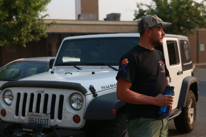 Wyatt Kuiken of South Bend, Pacific County, drove overnight from his home in Western Washington and slept in the parking lot of Omak City Hall to sign up as a volunteer firefighter Friday. He is trained to fight wildland fires through the state DNR. He couldn't make the time commitment to do so for this summer, but said he felt compelled to help during the current emergency. (Bettina Hansen / The Seattle Times)