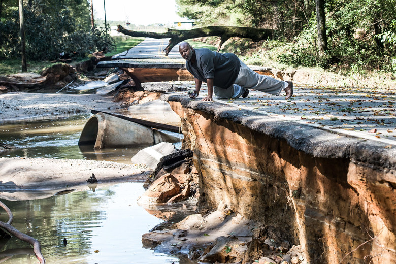 Trey McMillian looks over the damage done by flood waters on a road in Eastover on October 6, 2015 in Eastover, South Carolina. The state of South Carolina experienced record rainfall amounts over the weekend and continues to face resulting flooding. (Photo by Sean Rayford/Getty Images)
