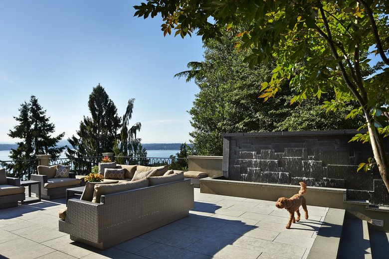 Riley, the family labradoodle, takes a stroll across the south terrace, with a large water feature, outdoor spaces to gather, dine and enjoy the garden. (Benjamin Benschneider/The Seattle Times)