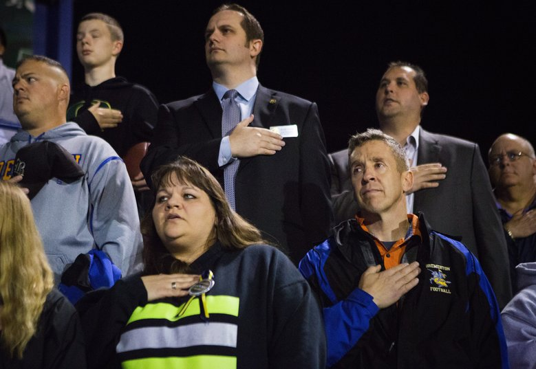 Bremerton assistant football coach Joe Kennedy, bottom right, recently placed on administrative leave over his prayers on the football field after games, listens to the national anthem from the stands at Memorial Stadium in Bremerton on Thursday, Oct. 29, 2015. The Satanic Temple of Seattle announced this week that they planned to be at the game on Thursday after a 12th-grader at Bremerton High School had requested the group perform a satanic invocation. (Lindsey Wasson/The Seattle Times)
