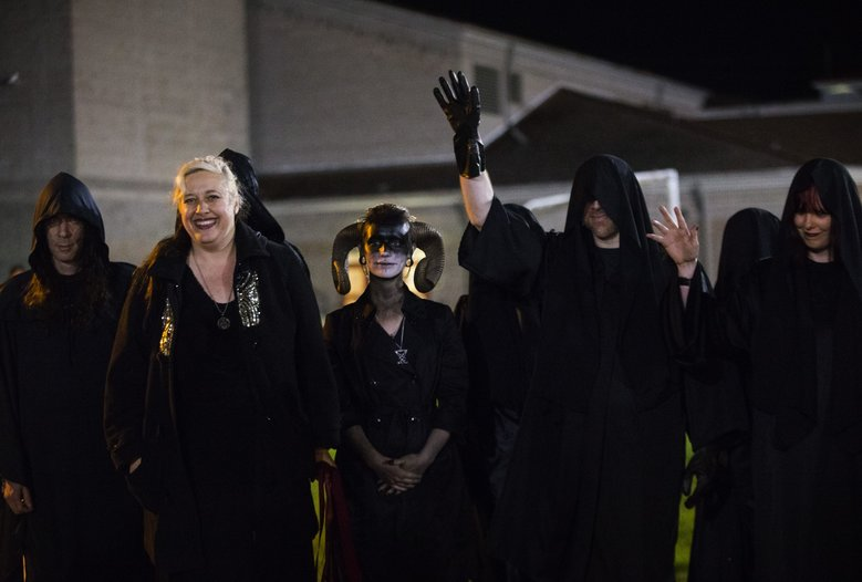 Members of the Seattle chapter of the Satanic Temple — outside Bremerton's Memorial Stadium because of the controversy over a coach's prayers on the football field — wave to yelling students during a game between the Bremerton Knights and the Sequim Wolves on Thursday. (Lindsey Wasson/The Seattle Times)