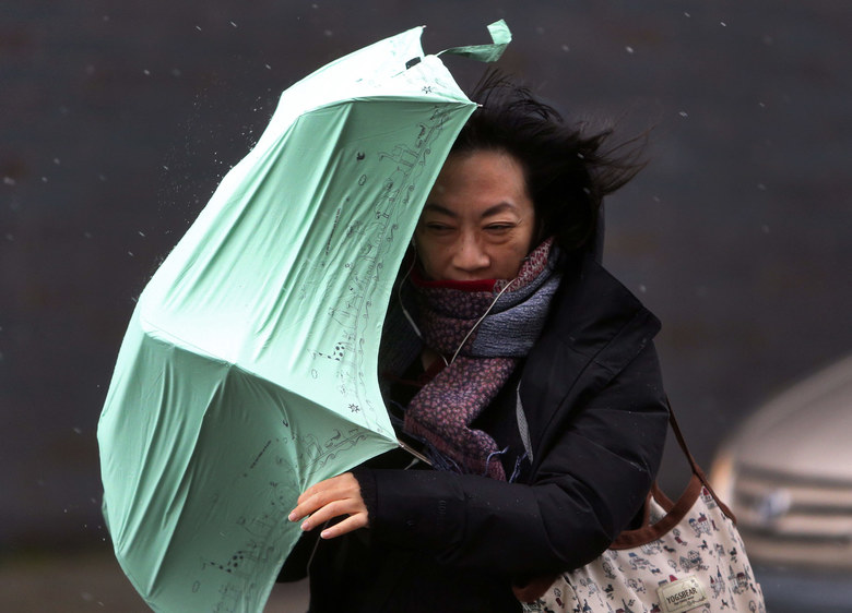 University of Washington graduate student Mia Ho is blasted by a wind gust while crossing The Ave en route to a class. (Ken Lambert / The Seattle Times)