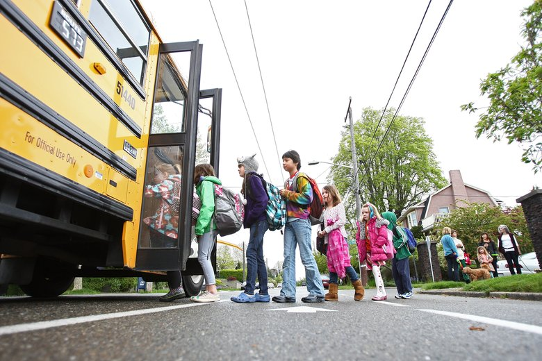 A group of students board their school bus in the Mt. Baker neighborhood in Seattle. (John Lok / The Seattle Times)
