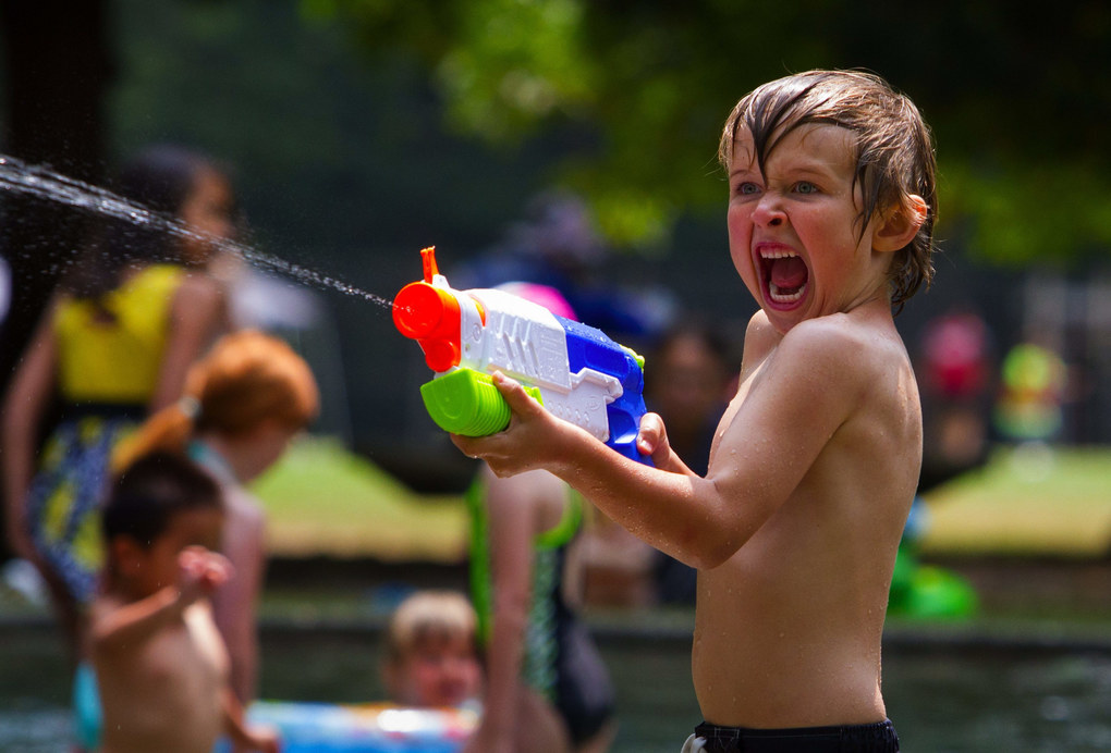 Five-year-old Cian Fitzgerald of West Seattle is full of enthusiasm as he shoots water out of his squirt gun at the Lincoln Park wading pool.   (Ellen M. Banner / The Seattle Times)