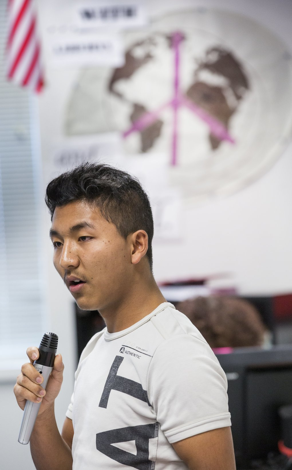 """Students at Foster High School prepare for the launch of """"Stories of Arrival, """" an anthology of poems about their journey to America. Kang Pu takes his turn reading his poem during class.  (Mike Siegel/The Seattle Times)"""