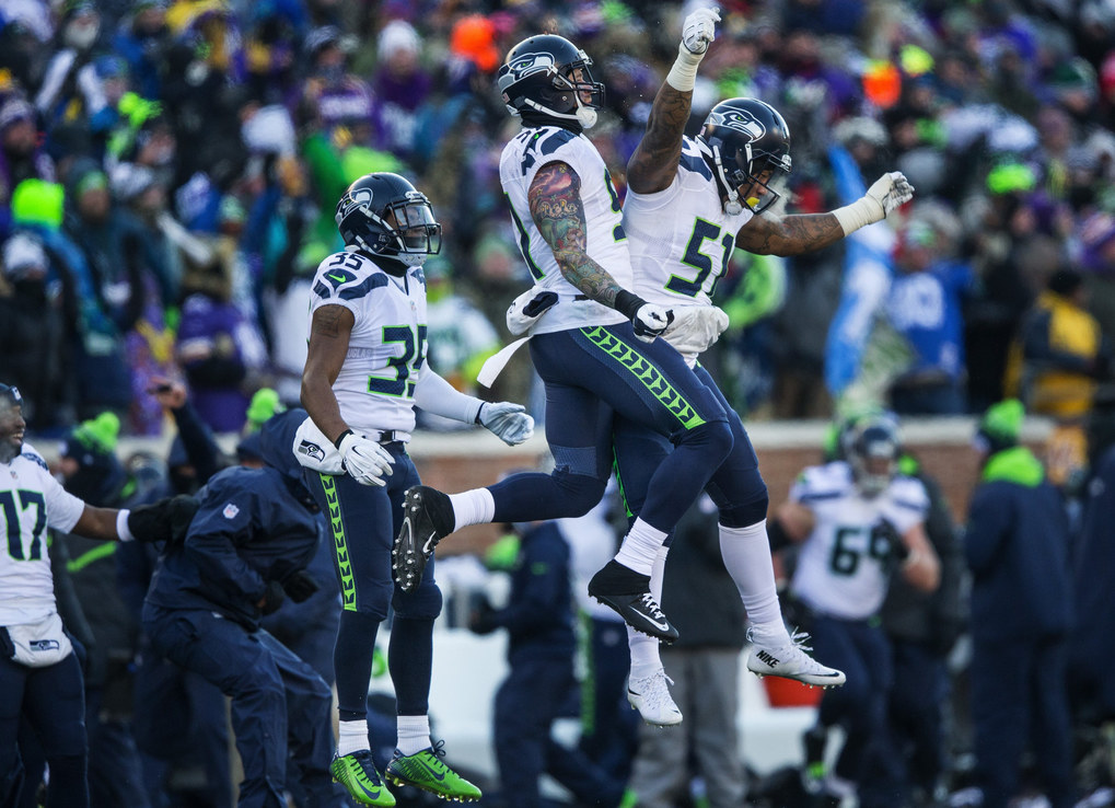 Seattle's defense celebrates its strip and fumble of Minnesota running back Adrian Peterson in the fourth quarter. (Dean Rutz / The Seattle Times)