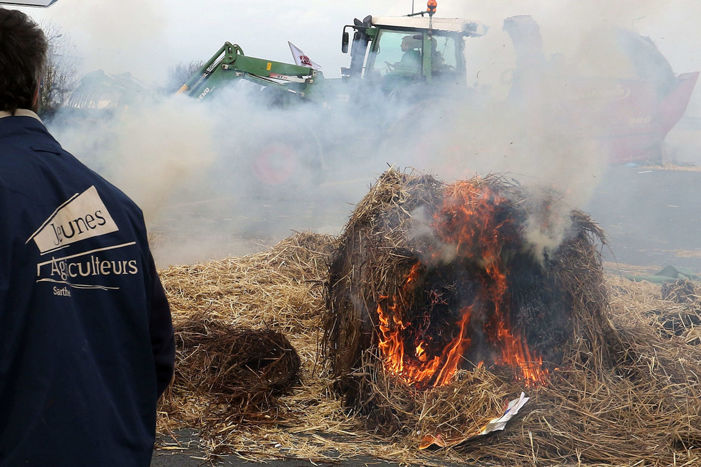 Bundles of hay are set on fire as part of an action b y French farmers who blocked roads in Le Mans, France, January 27, 2016.  They are protesting against the falling of prices from dairy and meat origin.  EPA/EDDY LEMAISTRE