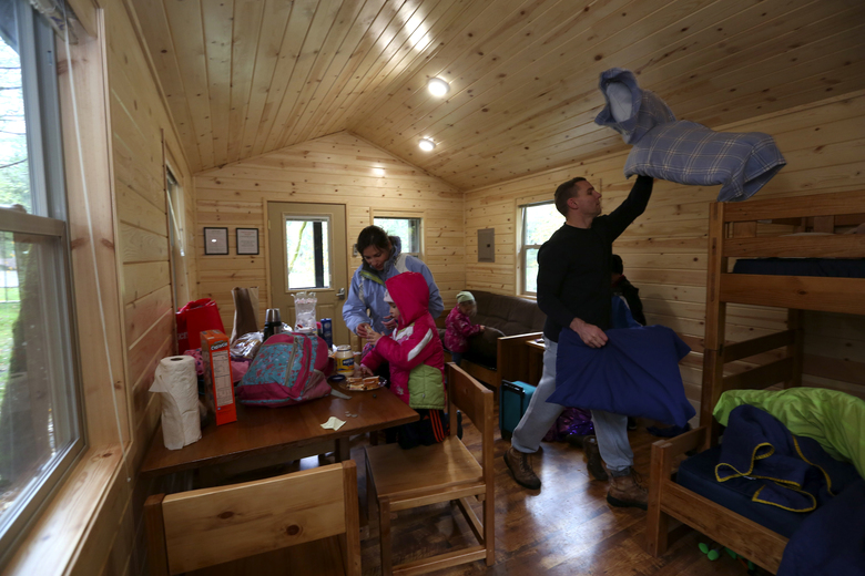 "The Thompson family, of Tacoma — mom Julianne, dad David and kids Simon, 8; Cecilia, 6; Emilia, 4; and Marilyn, 2 — unpack in their cabin at Dash Point State Park in Federal Way. ""We just wanted to find a place close by and get away from the daily grind,""   said Julianne Thompson. (Ellen M. Banner / The Seattle Times)"