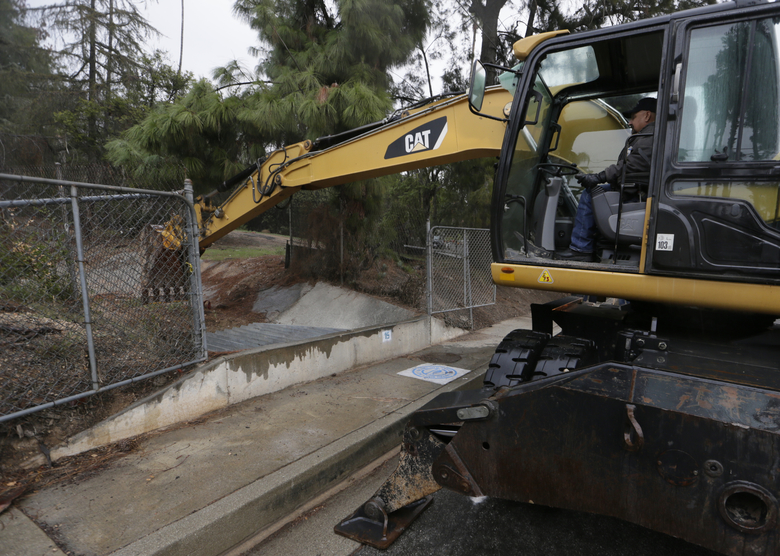 Los Angeles County Flood Control District crew member David Martinez uses an excavator to keep a flood inlet clean in Glendora, Calif., on Tuesday, Jan. 5, 2016. Persistent wet conditions could put some Los Angeles County communities at risk of flash flooding along with mud and debris flows, especially in wildfire burn areas. El Nino storms lined up in the Pacific, promising to drench parts of the West for more than two weeks and increasing fears of mudslides and flash floods in regions stripped bare by wildfires. (AP Photo/Damian Dovarganes)