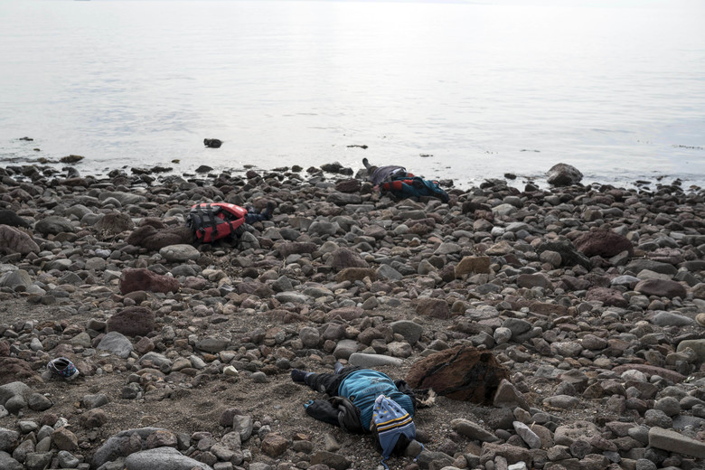 The lifeless bodies of migrants lay on the shoreline near the Aegean town of Ayvacik, Canakkale, Turkey, Saturday, Jan. 30, 2016. A boat carrying migrants to Greece hit rocks off the Turkish coast on Saturday and capsized, killing at least 33 people, including five children, officials and news reports said.  Some 75 other migrants were rescued. A Turkish government official said he expects the death toll from the incident to rise as rescue workers try to reach other migrants believed trapped inside the wreckage of the boat which sank shortly after departing from the Aegean resort of Ayvacik.(AP Photo/Halit Onur Sandal)