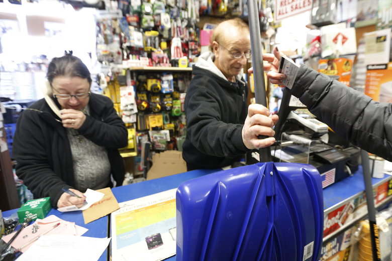 Vinny Pisciotta, center, sells a snow shovel to Donna Przychodzki, of Secaucus, N.J., as his sister-in-law Margaret Pisciotta, left, takes a call at Meadowlands Hardware, Friday, Jan. 22, 2016, in Rutherford, N.J. Towns across the state are hunkering down in preparation for a major snowstorm expected to begin later in the day. (AP Photo/Julio Cortez)