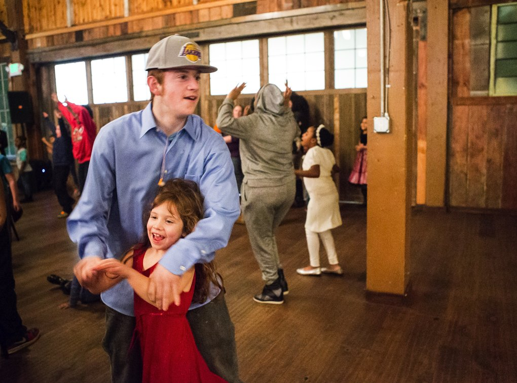 Big brother Tyrus Gilbertson whisks around sister Corrine, 6, as they dance to tunes from the Michael Benson Band during a special, donated event for Mary's Place families at Sodo Park on Saturday. (Lindsey Wasson/The Seattle Times)
