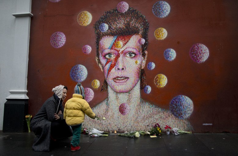 "A woman and child place a flower alongside other tributes beside a mural of British singer David Bowie by artist Jimmy C in Brixton, south London, Monday, Jan. 11, 2016. David Bowie, the iconic and shape-shifting British singer whose illustrious career lasted five decade with hits like ""Fame,"" ""Heroes"" and ""Let's Dance,"" died Sunday after a battle with cancer. He was 69. The singer, who was born David Jones at the family home in the Brixton area of London, came of age in the glam rock era of the early 1970s. (AP Photo/Matt Dunham)"