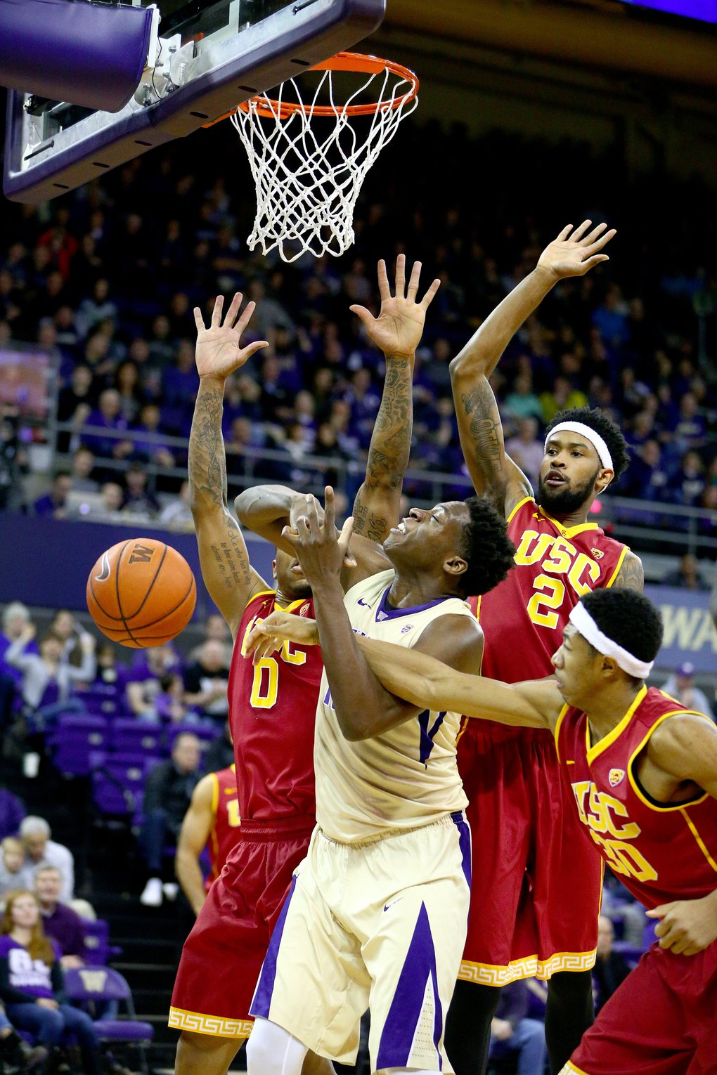 Washington's Noah Dickerson is caught in a triple-team under the basket in the first half. (John Lok/The Seattle Times)