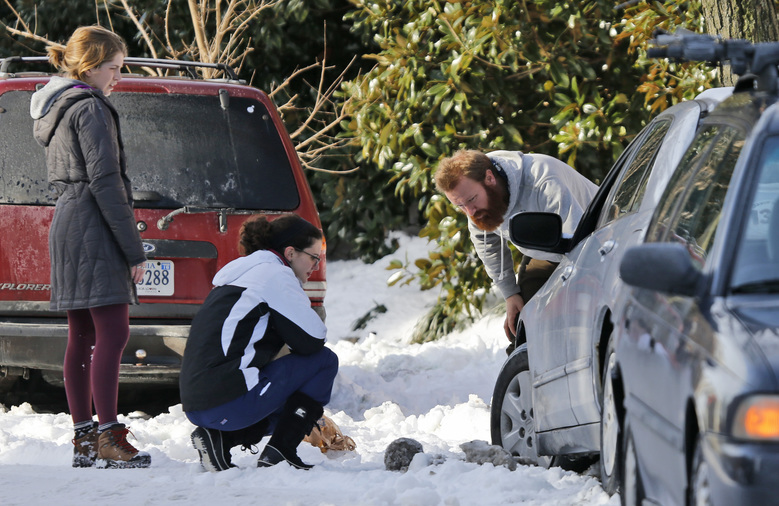 Taryn Payne, left, of Richmond,  Laura Pape, center, of Wellsville N.Y., and Brandon Jones, of Richmond, right, work at freeing a stuck car in Richmond, Va., Monday, Jan. 25, 2016.  Area residents continue to dig out from the weekend's snowstorm.  (AP Photo/Steve Helber)