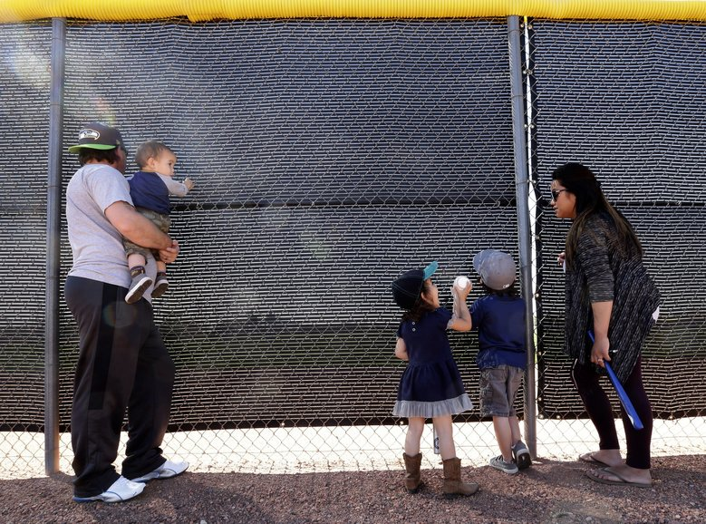 Fans watch through a fence during spring training baseball practice for the Seattle Mariners Saturday, Feb. 20, 2016, in Peoria, Ariz. (AP Photo/Charlie Riedel)
