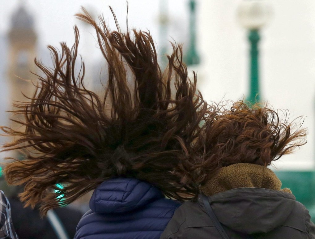 Two women walk with their fly-away hair during a windy day in San Sebastian, the Basque Country, northern Spain,  on Saturday. The Iberian Peninsula is under a spell of rough weather with strong winds and snow level rising in the north and centre of the country.    (JUAN HERRERO / EPA)