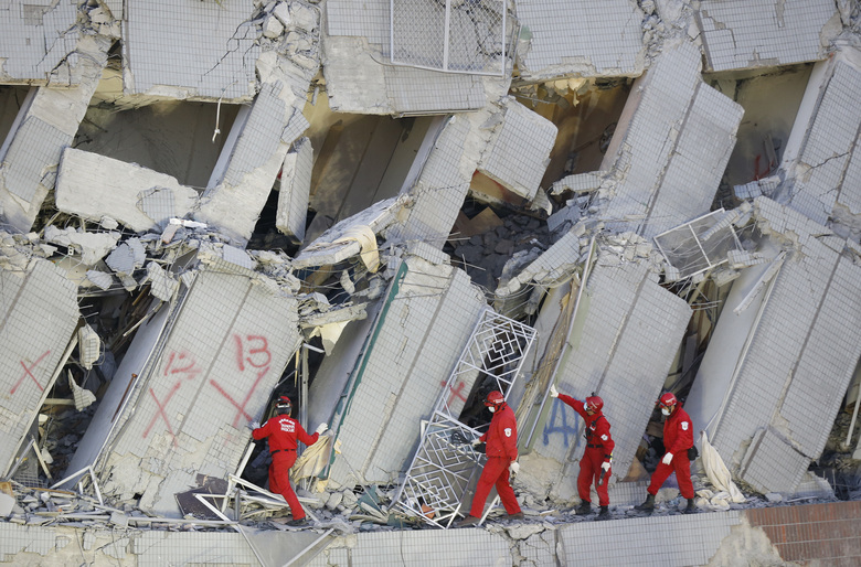 Emergency rescuers continue to search for missing in a collapsed building from an earthquake in Tainan, Taiwan, Sunday, Feb. 7, 2016. Rescuers on Sunday found signs of live within the remains of the high-rise residential building that collapsed in a powerful, shallow earthquake in southern Taiwan that killed over a dozen people and injured hundreds. (AP Photo/Wally Santana)