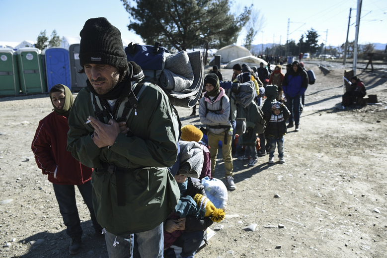Migrants line up as they wait to cross the borderline with Macedonia from the northern Greek village of Idomeni, on Saturday, Feb. 6, 2016. European Union foreign ministers anxious to stem the flow of migrants coming through the Balkans are discussing with their counterparts from the region better ways to protect borders. With Greece unable to control the thousands of migrants making the crossing from Turkey, some EU nations are now looking to help non-member Macedonia stop them at its southern border before they get to the European Schengen zone of border-free travel.  (AP Photo/Giannis Papanikos)