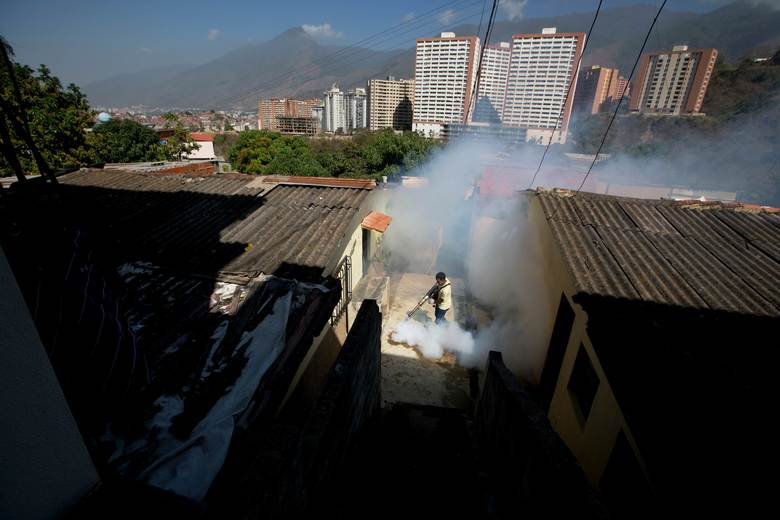 A Sucre municipality worker fumigates for Aedes aegypti mosquitoes that transmit the Zika virus in the Petare neighborhood of Caracas, Venezuela, Monday, Feb. 1, 2016. Venezuela is reporting a jump in cases of a rare, sometimes paralyzing syndrome that may be linked to the Zika virus. (AP Photo/Fernando Llano)
