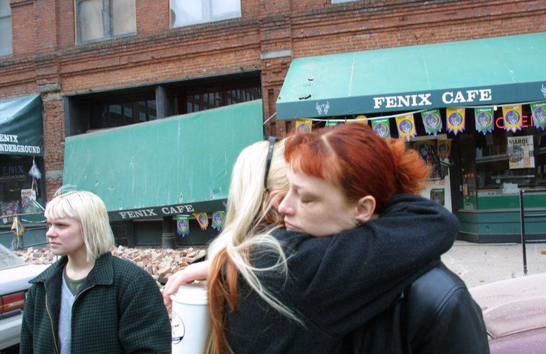 Employees hug one another outside the Fenix Cafe in Pioneer Square. Both had just shown up for work as the Nisqually quake struck.  (Alan Berner/The Seattle Times)