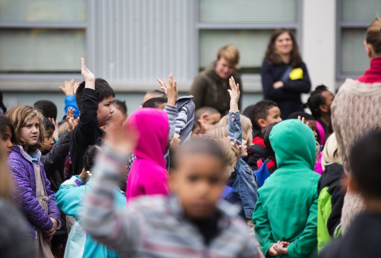 Kids raise their hands as De'Vaughnn Williams, Miss Black Washington USA, asks them how many speak other languages at home during a Rally for Unity, Service & Peace to celebrate Black History Month on the playground at Madrona K-8 School on Friday.  (Lindsey Wasson/The Seattle Times)