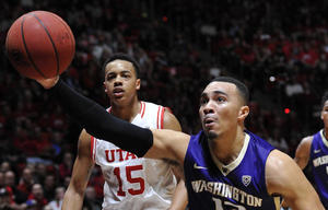 Washington guard Andrew Andrews grabs a loose ball in front of Utah guard Lorenzo Bonam during the second half of the Utes' 90-82 win over the Huskies on Feb. (Gene Sweeney Jr. / Getty Images)