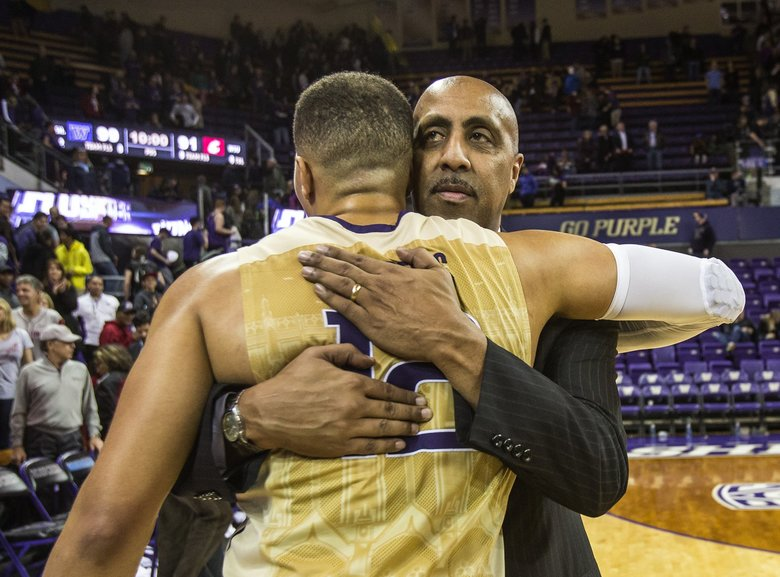Lorenzo Romar has a hug for Andrew Andrews following Andrews' final game of his regular season collegiate career.    (Dean Rutz / The Seattle Times)