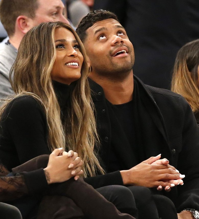Singer Ciara, left, and Seattle Seahawks quarterback Russell Wilson look at a a huge video screen as they sit courtside in the first half of an NBA basketball game between the New York Knicks and the Washington Wizards at Madison Square Garden in New York, Tuesday, Feb. 9, 2016. (AP Photo/Kathy Willens)