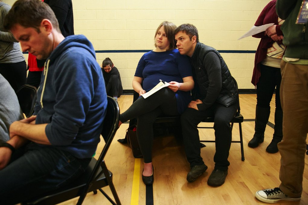 Catherine Roth and her husband Evan Welbourne listen to speakers during the Washington state caucuses at Martin Luther King, Jr. Elementary School in Seattle.  (Erika Schultz / The Seattle Times)