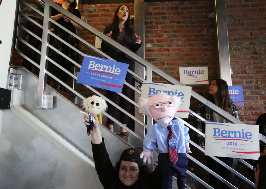 Bernie Sanders supporter Leslie Zukor, of Mercer Island, brought Bernie dolls to the grand opening of Sanders' Seattle campaign office on Sunday. Above Zukor is Dulce Saenz, Washington State campaign director, who fired up a packed room of supporters. (Ken Lambert / The Seattle Times)