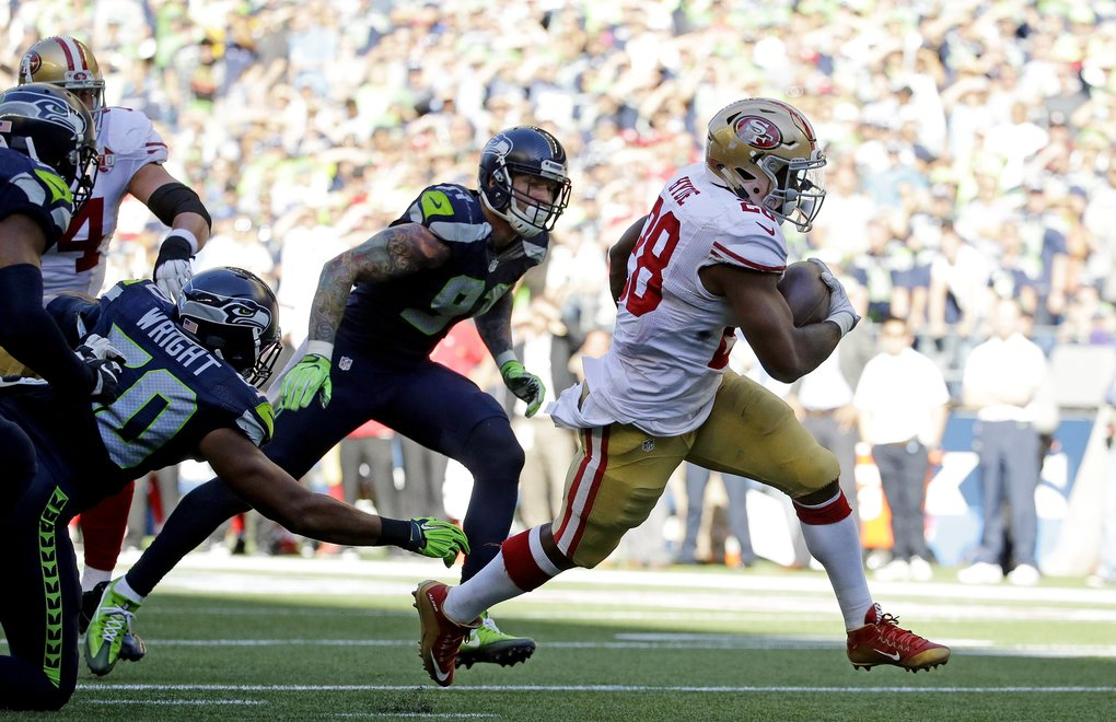 San Francisco 49ers' Carlos Hyde, right, scores a touchdown against the Seattle Seahawks in the second half of an NFL football game, Sunday, Sept.