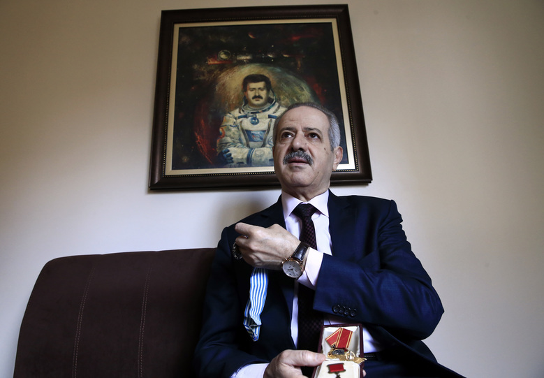 Syrian Muhammad Faris,  Syria's first cosmonaut and a former general of the Syrian Air Force, backdropped by a paining of him depicting him with a space suit, smiles as he  talks while holding his Soviet-era and international medals, in Istanbul, Monday, March 7, 2016. Gen. Mohammed Faris made history and turned into a national hero in 1987, when he became Syria's first man in space as part of a Soviet-led mission.  Now, as refugee in Turkey, the 64-year-old cosmonaut is critical of Russia's intervention in Syria and wants European nations to help remove Syrian President Bashar Assad from office to bring about an end to the refugee crisis.  (AP Photo/Lefteris Pitarakis)