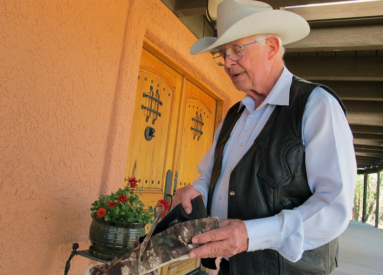 "In this Tuesday, March 15, 2016 photo, Jim Chilton shows off what are known as ""carpet shoes"" that he has collected from his sprawling property over the years in Arivaca, Ariz. The makeshift slip-on shoes with carpet on the soles are worn by people illegally crossing the border as a way to keep authorities from finding their tracks. (AP Photo/Brian Skoloff)"