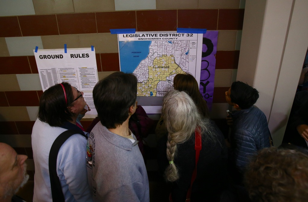 Democratic voters surround a map of the 32nd Congressional District to locate their precinct during the caucus at Edmonds-Woodway High School in Edmonds, Saturday, March 26, 2016.  (Sy Bean / The Seattle Times)