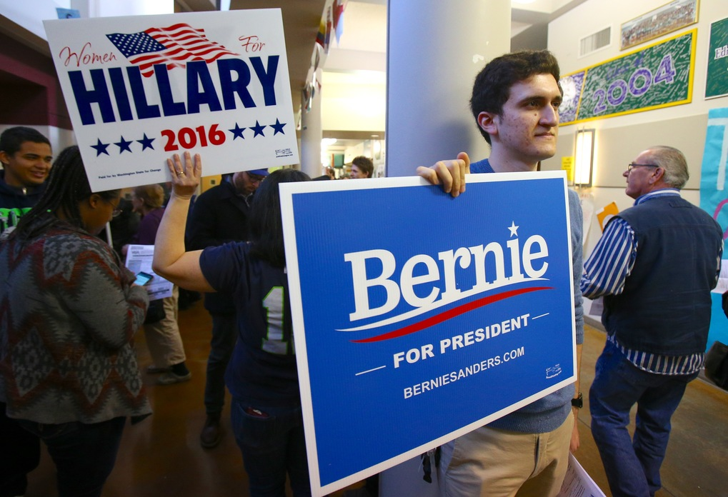 """Voter Josh Meusch holds a Bernie sign at Edmonds-Woodway High School for the 32nd Congressional District caucus Saturday, March 26, 2016. """"There's a lot of energy,"""" said Meusch. """"Regardless of who wins, it's awesome.""""(Sy Bean / The Seattle Times)"""