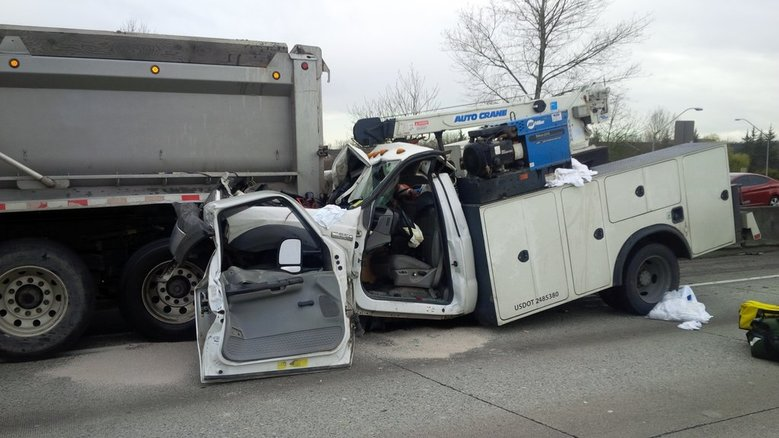 The driver of the pickup at right suffered severe injuries after his vehicle was pinned under a  dump truck Thursday on Interstate 405 in Renton. (Washington State Patrol photo)