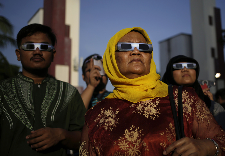 People look up at the sun wearing protective glasses to watch a solar eclipse in Jakarta, Indonesia, Wednesday, March 9, 2016. The rare astronomical event is being witnessed Wednesday along a narrow path that stretches across 12 provinces encompassing three times zones and about 40 million people. (AP Photo/Dita Alangkara)